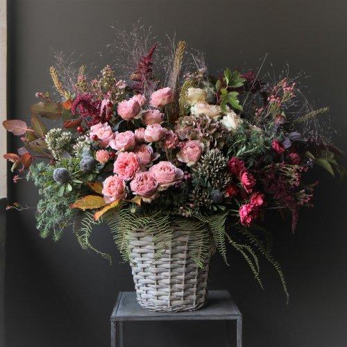 モーヴ系のバラのグラデーションカラーにダーク色合い葉物を合わせた季節のアレンジメント。