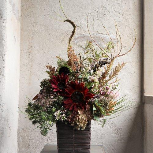 ダークな色合いのひまわりに石化柳や枝物など合わせたモダンなアレンジメント。